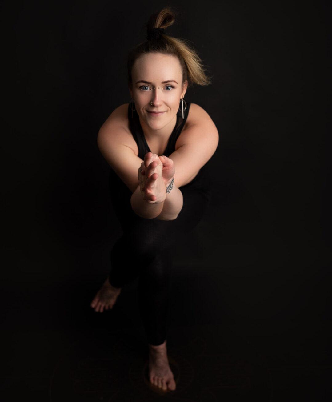 Na ciemnym tle uśmiechnięta kobieta w jednej z figur jogi.