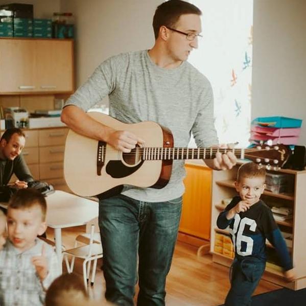 Mężczyzna stoi, grając na gitarze, dookoła niego tańczą uśmiechnięte dzieci.