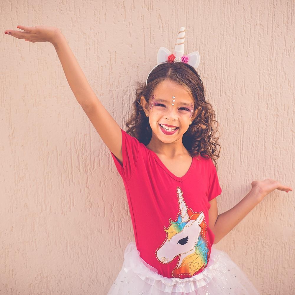Uśmiechnięta dziewczynka w czerwonej koszulce z jednorożcem i baletowej tiulowej spódniczce. na głowie ma opaskę jednorożca. Ręce rozłożone na boki w tanecznej pozie, jedna wyżej, druga niżej.