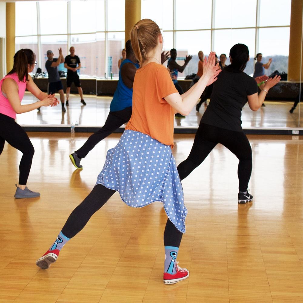 Na sali gimnastycznej na przeciwko lustra grupa tańczących osób, klaszczą w dłonie, wszyscy zwróceni są w jednym kierunku.