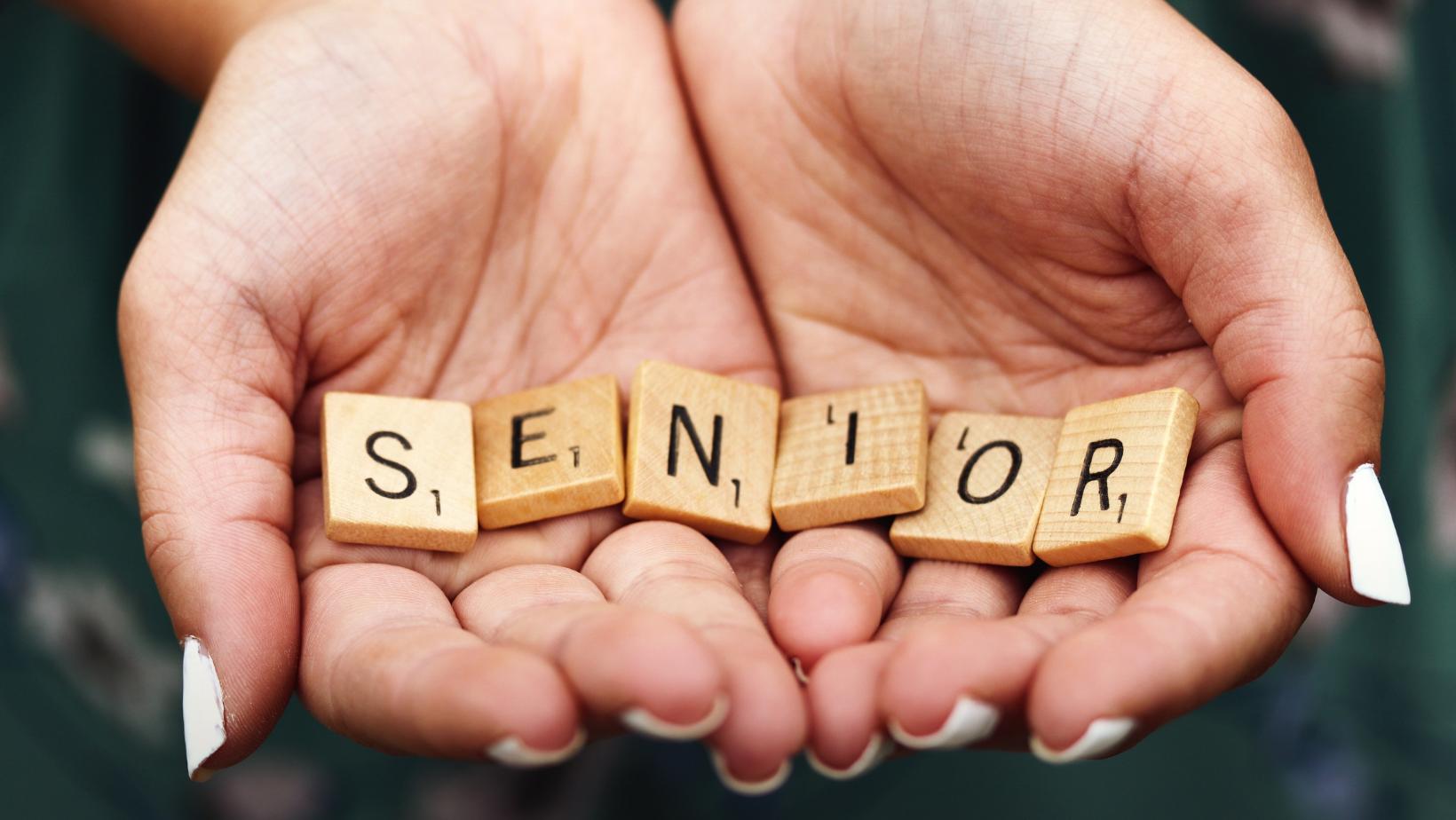 """Na dłoniach przylegających do siebie z literek od scrabble ułożony napis """"senior"""""""