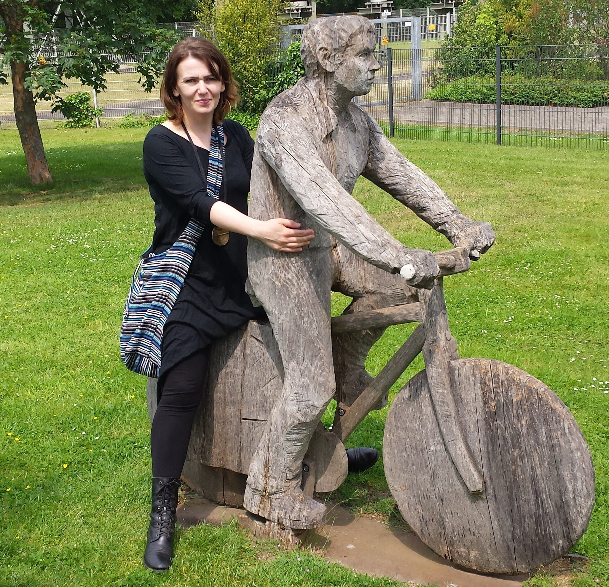 Kobieta siedzi na kamiennej rzeźbie w kształcie postaci człowieka na rowerze.