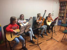 Dzieci z gitarami w rękach, siedzą na krzesłach i przed kokpitami z nutami.