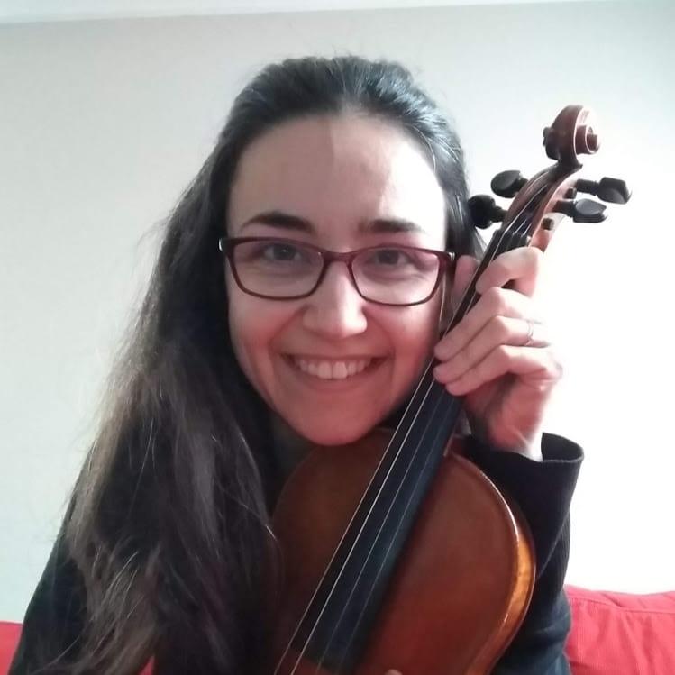 Uśmiechnięta kobieta o ciemnych włosach, w okularach, przytula do siebie skrzypce.