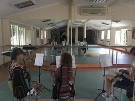 Na sali w lustrzanym odbiciu grupa dzieci - siedzą z instrumentami przed kokpitami z nutami.