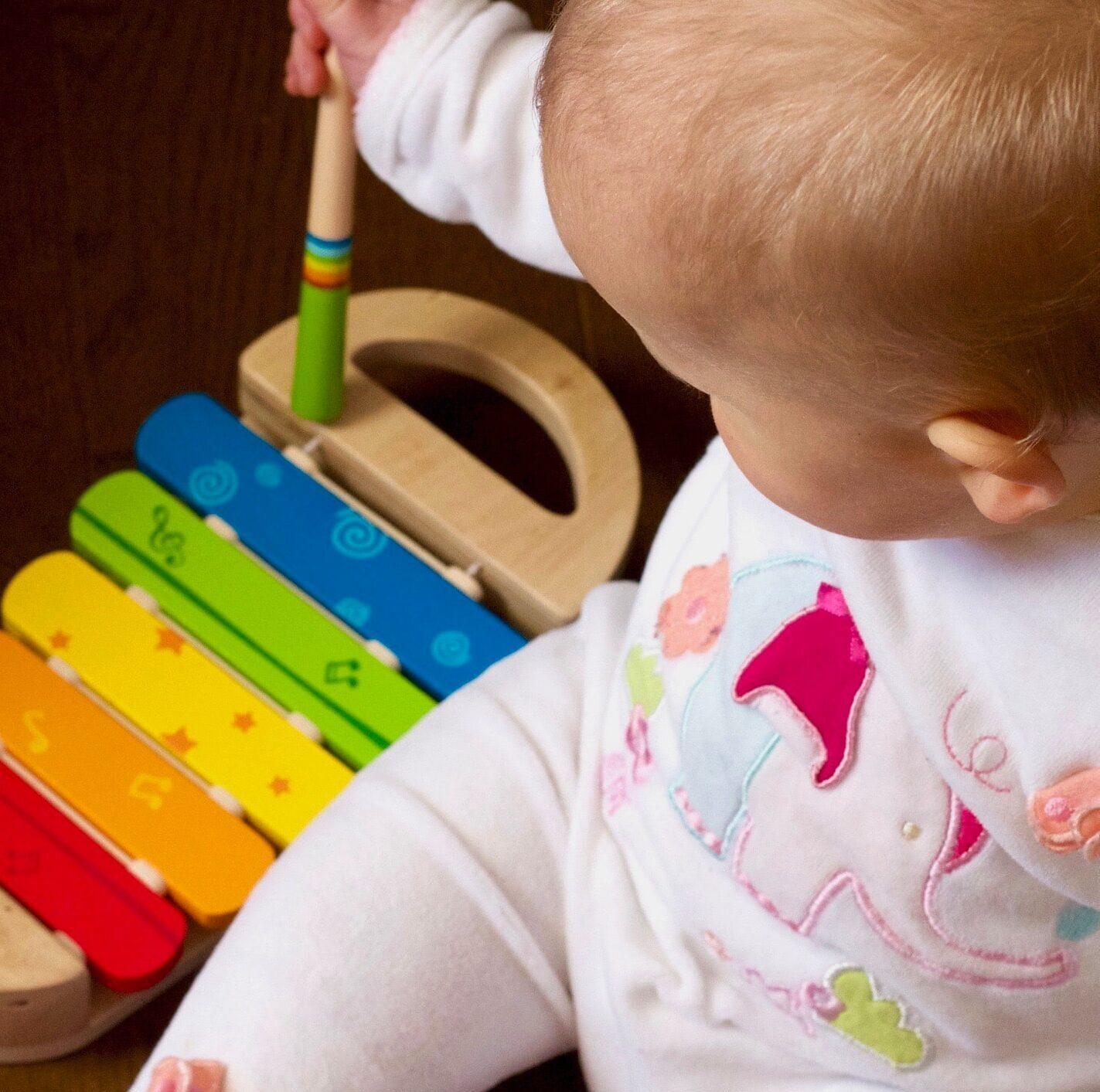 Małe dziecko z białych śpioszkach siedzi obok kolorowych cymbałków i trzyma pałeczkę do grania.