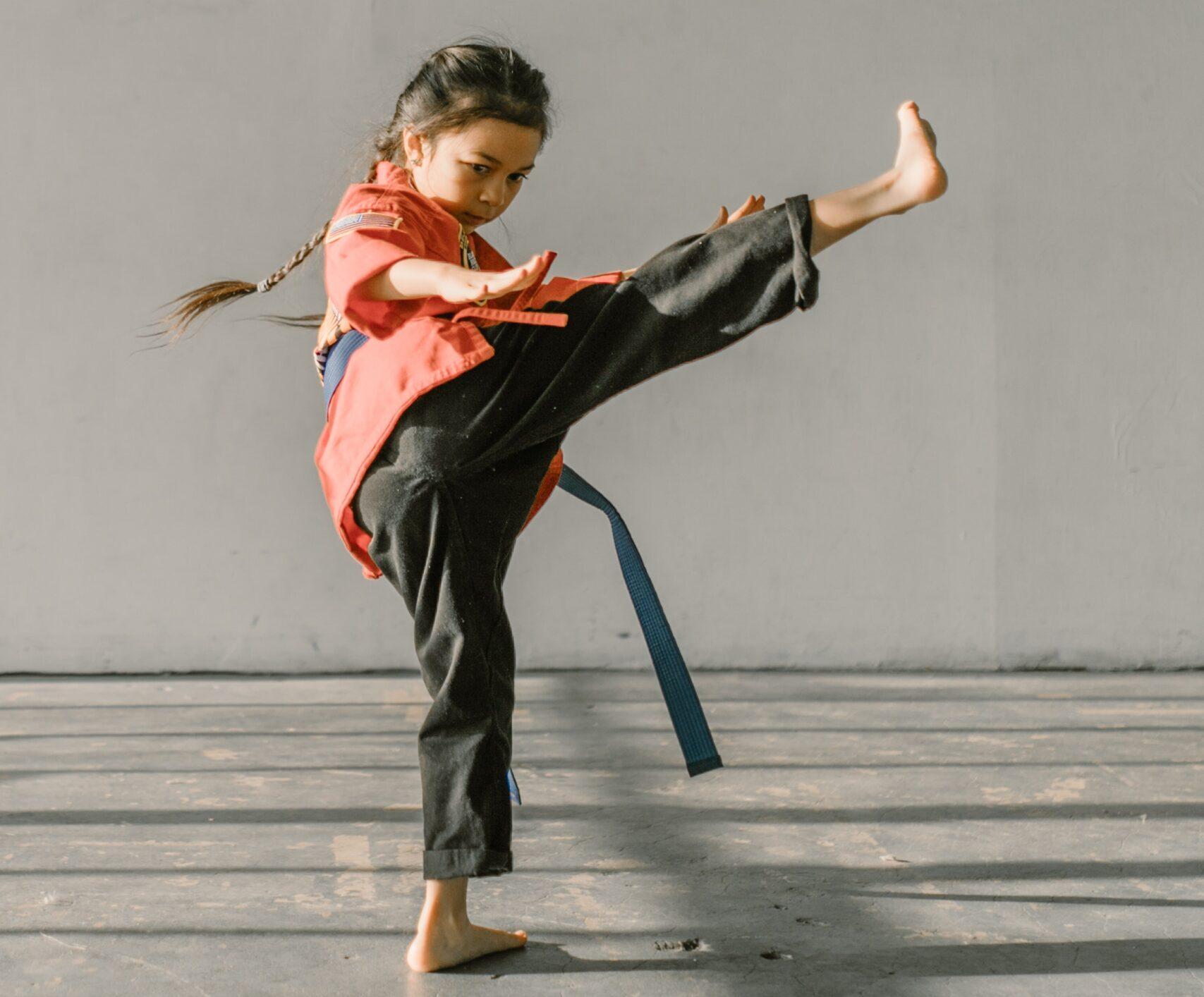 Dziewczynka w pozie jiu-jitsu, prawą nogą robi wykop w górę.