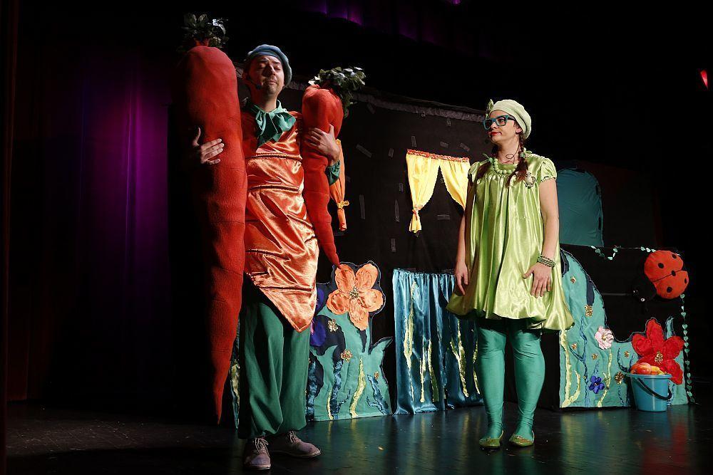 Na scenie kolorowa scenografia i dwoje aktorów w kolorowych strojach. Mężczyzna trzyma dwie duże uszyte z materiału marchewki, kobieta stoi patrzy na niego.