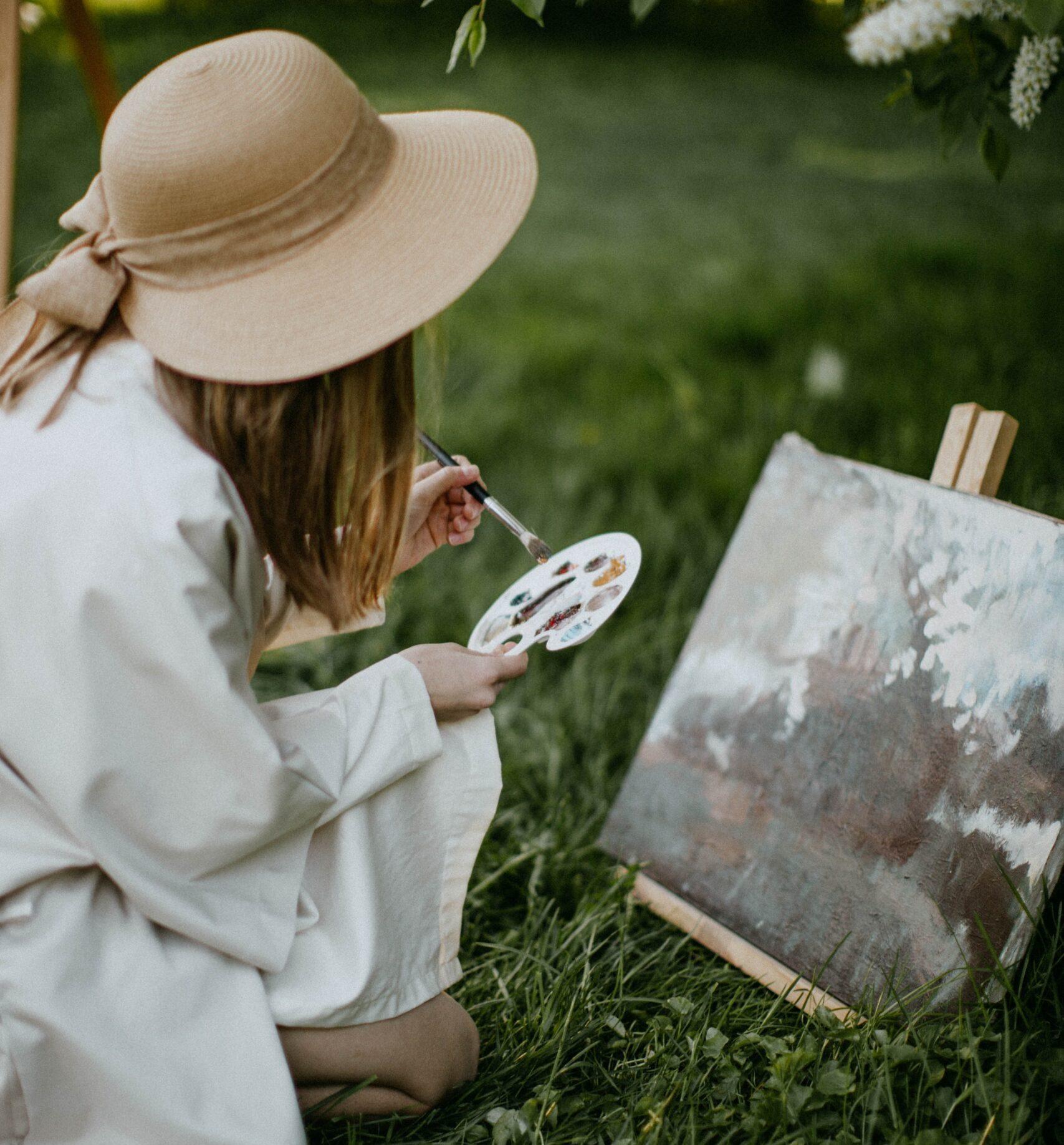 Kobieta w kapelusz ze słomy, maluje w plenerze na trawie ma ustawioną sztalugę i płótno, w dłoniach trzyma pędzel i paletkę z farbami.